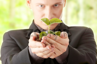 Man in suit holding smal plant in his hands