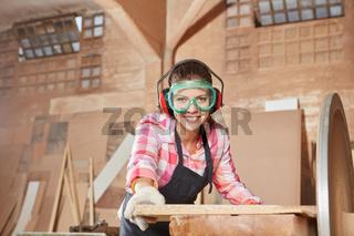 Frau in Tischler Lehre schleift Holz