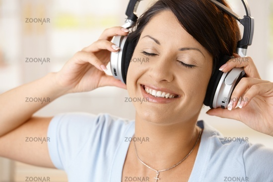 Happy woman enjoying music on headphones