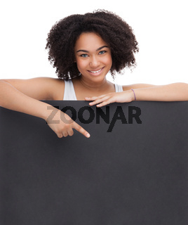 Young Smileing teenager african girl hold black blank paper and shows on it.
