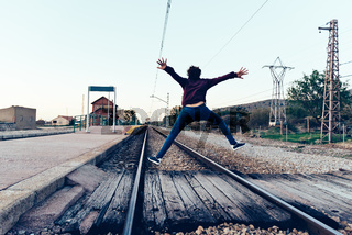Young woman is jumping on the railroad tracks at old railroad station