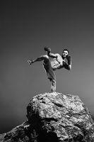 Monochrome shots of a fierce male boxer training outdoors