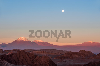 Full-moon in the Moon Valley. Volcanoes Licancabur and Juriques, west of San Pedro de Atacama, Chile in the Cordillera de la Sal, in the Atacama desert of Chile