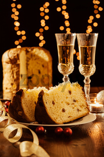 Sliced italian panettone, sparkling wine and decorations
