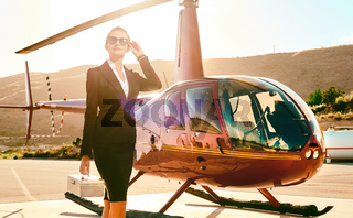 Elegant business woman near the helicopter.
