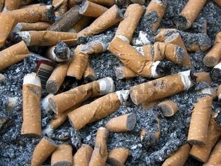 Zigarettenkippen mit Zigarettenasche und einer Zigarettenschachtel