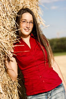 Junge Frau an Stroh gelehnt