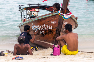 Thai men painting a longtail boat