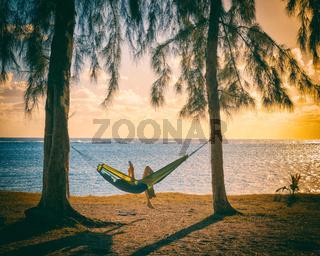Reading tablet in hammock at sunset