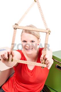 junge Frau mit Haussymbol zwischen Umzugskartons