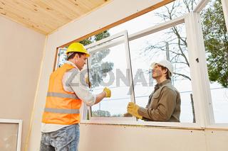 Monteure bauen in Teamwork Fenster ein