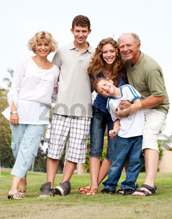 Affectionate family of five posing outdors on sunny day