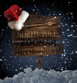 Wooden sign with Santa hat on snowy background
