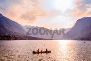 Family rowing in canoe boat on beautiful lake Bohinj, Slovenia.