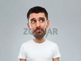 unhappy young man over gray background