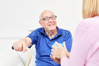 Lächelnder Senior wird betreut in häuslicher Pflege