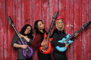 3 mädchen mit plastikgitarren vor einer fotobox