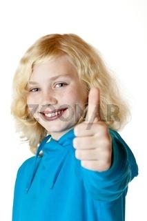 Junges hübsches glückliches Mädchen / Kind zeigt Daumen nach obe