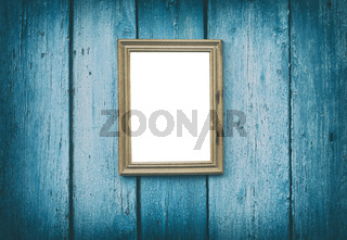 empty wooden frame hanging on blue cracked wooden wall