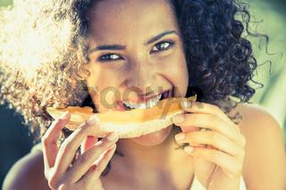 Junge Frau isst Melone an einem sonnigen Tag, Gegenlicht