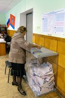 Woman puts the ballot in the ballot box at polling stations on the day of elections to the State Duma