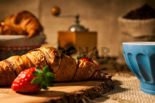 Closeup of a continental breakfast with croissant and a cup of milk