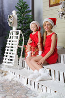 happy mom and daughter in Christmas costumes are sitting under snow