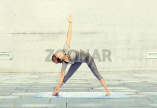 woman making yoga triangle pose on mat