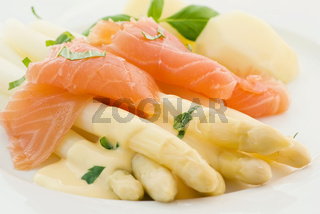 Asparagus with salmon slices and potatoes on a white plate