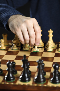 Hand moving pawn on chess board