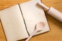 Kochbuch, Kochlöffel und Nudelholz auf Holz