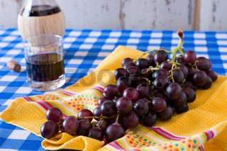 Closeup of a bunch of red grapes and a glass of red wine