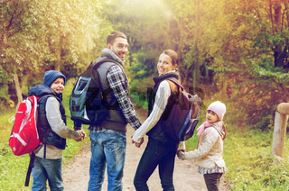 happy family with backpacks hiking