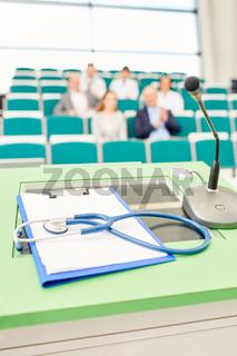 Stethoskop und Klemmbrett im Uni Hörsaal
