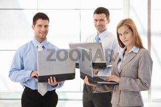Confident businessteam working on laptop smiling