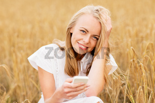 happy young woman with smartphone on cereal field