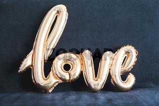 Shaped golden balloon of word Love on dark background