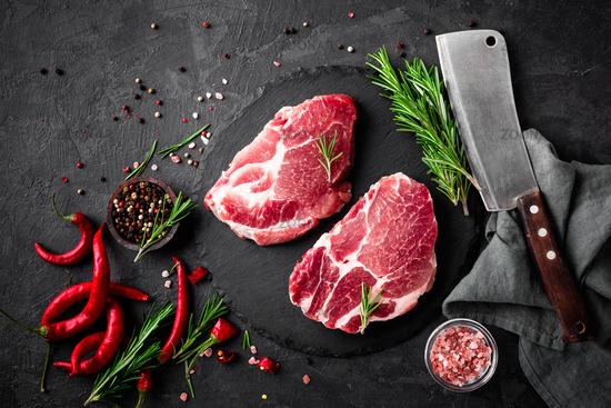 Raw pork meat. Fresh steaks on slate board on black background. Top view