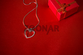 Heart pendant on a red satin background