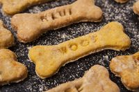 Homemade oatmeal dog treats with carrots on black background
