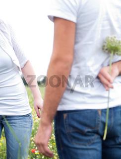 Close up shot of a boyfriend hiding a flowerr in the park