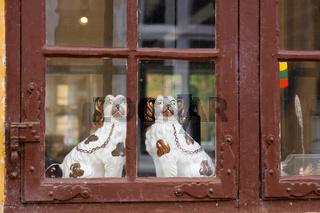 Zwei weiße Porzelanhunde in einem Fenster
