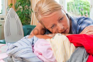 Hausfrau beim Bügeln mit Bügeleisen und Wäsche.