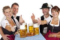 Bayrische Mädchen und Männer mit Maß Bier halten Daumen nach oben. Freigestellt auf weissem Hintergrund