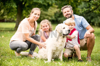 Glückliche Familie mit Hund im Garten
