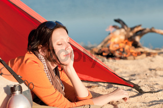 Camping woman relax in tent by campfire