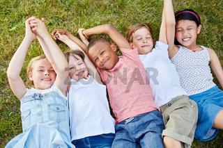 Kinder als Team liegen auf einer Wiese