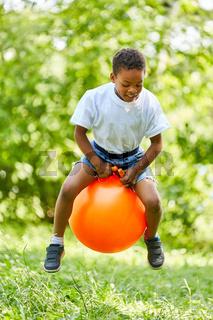 Afrikanischer Junge hüpft auf einem Hüpfball