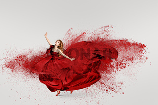 Fashion woman dancing in fluttering red long dress with cloud of flour powder