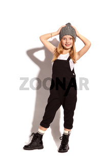 little girl in dark overall on the white background